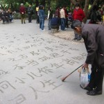 Elderly writing Chinese on pavement with water